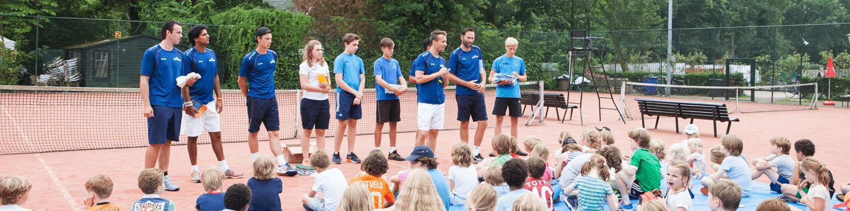 Trainer tennis op maat legt uit bij tenniskamp Kattenlaan